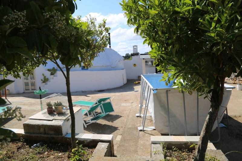 External view with the above ground pool and sunbeds.