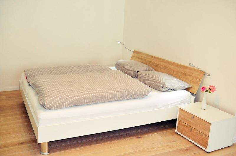 Light oak wooden planks and comfortable double bed. Bright Oak country house planking, good bed.