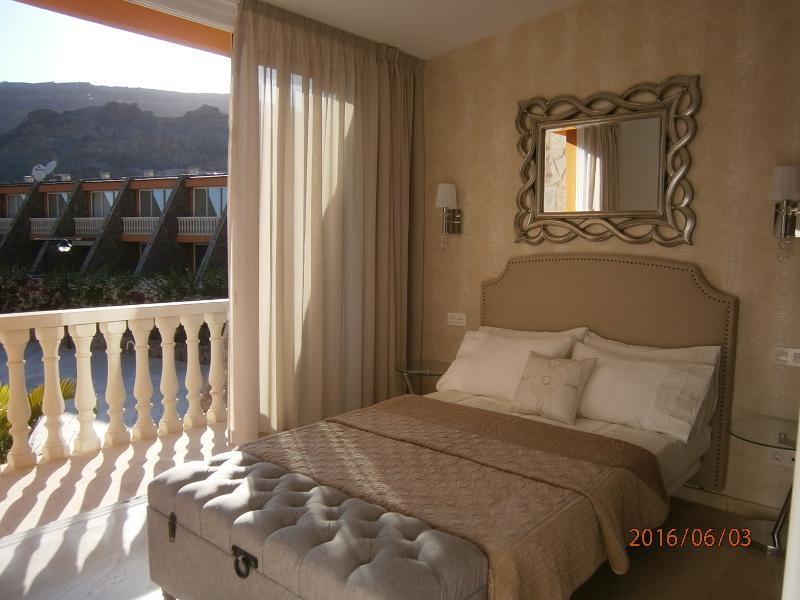 bedroom1 with patio doors and balcony with seating area overlooking pool