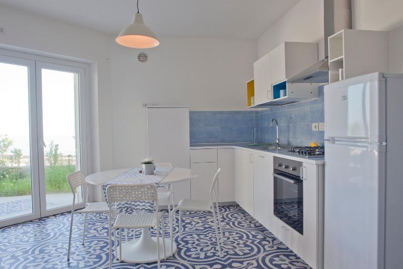 Cucina con porta/finestra a vista.