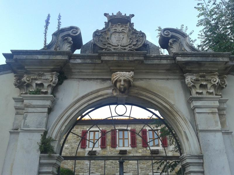 The 18th century entrance gate with a view of Palazzo Portole inside the landscaped garden