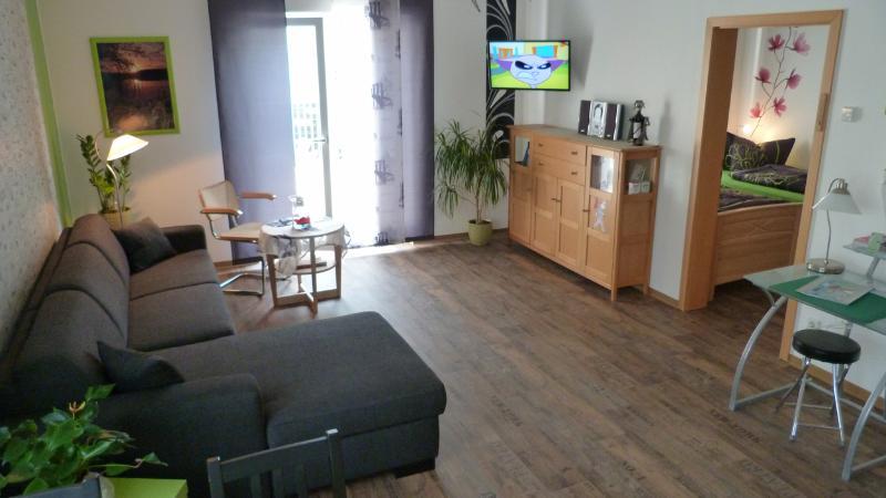 Wohnbereich mit Fernseher und Fenstertür zur Terrasse