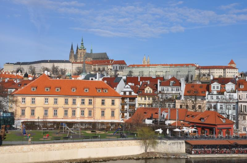 View from across the river to the apartment house with Prague Castle towering behind