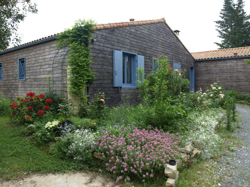 maison en bois sur un joli terrain boisé et fleuri en bord de mer