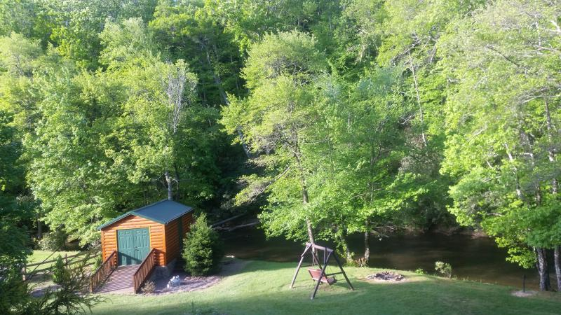 view form front porch of the shed and swing by the river.