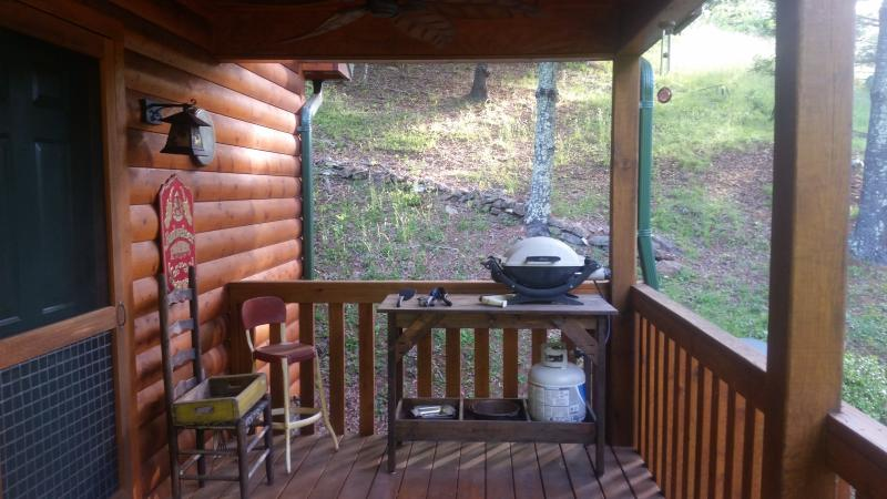 gas grill on porch with untensils