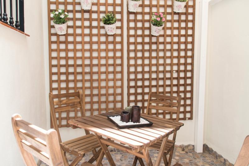 Patio / Terraza con mesa y sillas de madera. Pared emulando patio andaluz. Ideal para tomar un vino