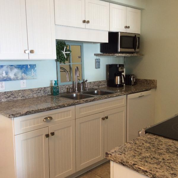 cocina costera con encimeras de granito y utensilios de cocina completamente equipada, vajilla y cristalería