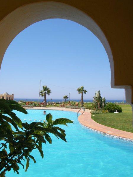 Uitzicht op het zwembad uit de gemeenschappelijke tuin