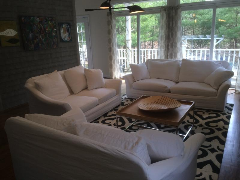 Large family room opens to deck overlooking pool, fireplace, comfy furniture, 55 inch smart TV.