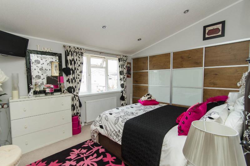 quarto principal com cama king size com roupeiros de correr modernos e TV / DVD