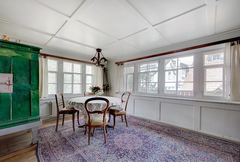 Stube mit Esstisch, Sofa, Einzelbett, Kachelofen, Zentralheizung und Fenstern zum eigenen Balkon