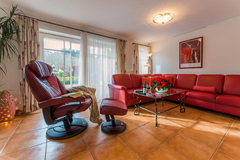 Wohnzimmer von Fewo GRANAT mit Ledercouch und Luxus-TV-Sessel, bodentiefe Fenster mit Elektrorollos