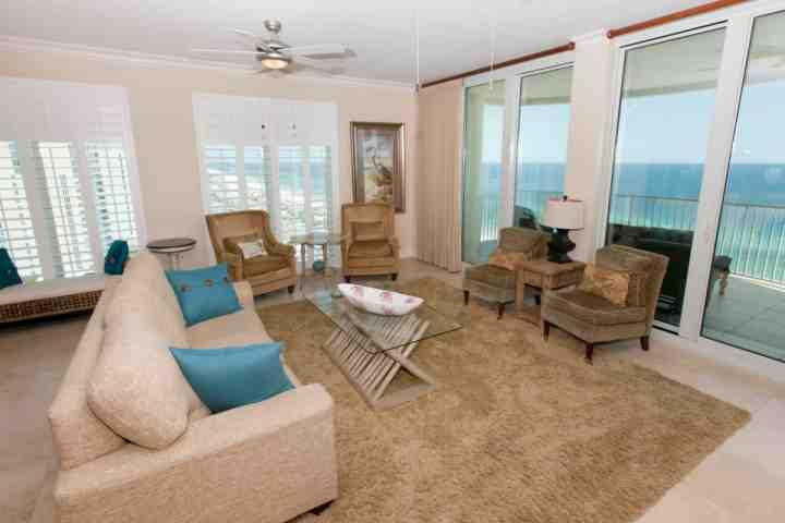 Séjour avec des sièges pour 7, ventilateur de plafond et accès porte coulissante sur un balcon donnant sur le golfe