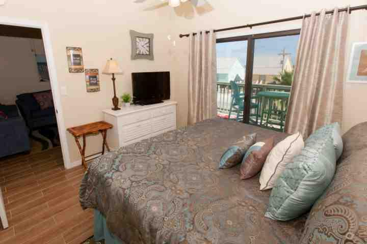 Master bedroom with flat screen TV and private access to balcony