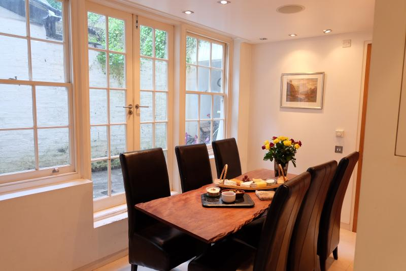 Bright dining room overlooking tiny outdoors and well sized kitchen