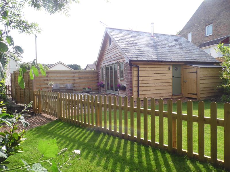 Sunny  garden and patio  which has a lovely wooden love seat and a secure bike store.