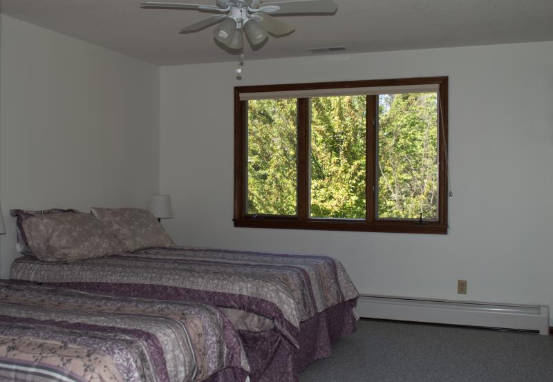 View of west bedroom with one double and one twin sized bed