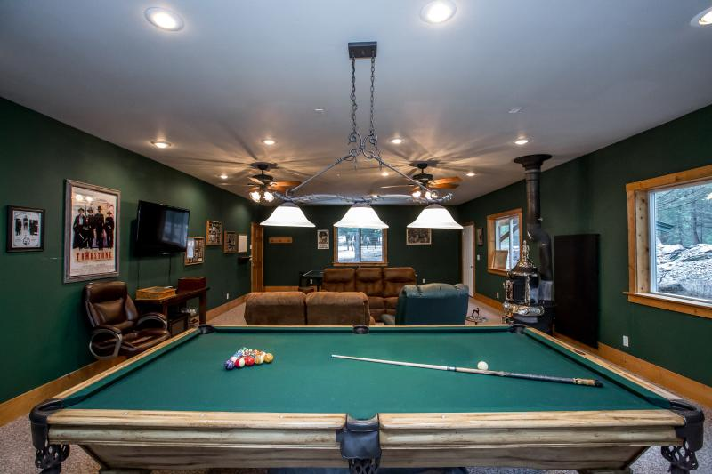 Man cave with TV, wood burning stove, pool table & ping pong table and comfortable furniture.