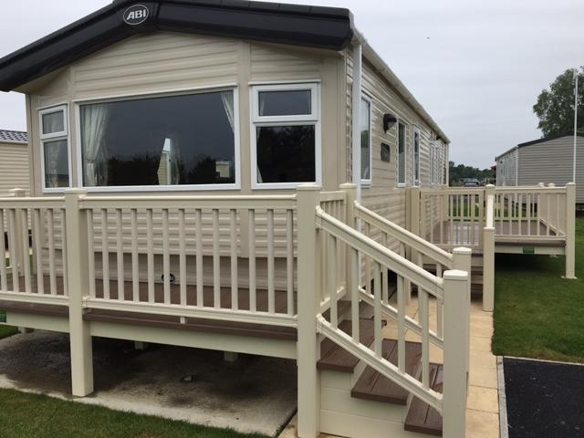 2016 luxury caravan with own parking together with  table and chairs outside on the decking area