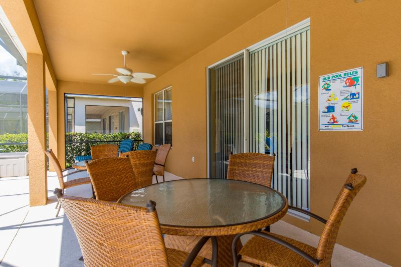 Screened and covered lanai area with seating for the whole family