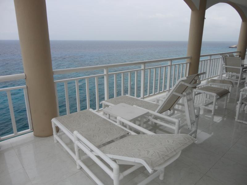 The covered oceanfront terrace has loungers, a dining table and hot tub/spa.
