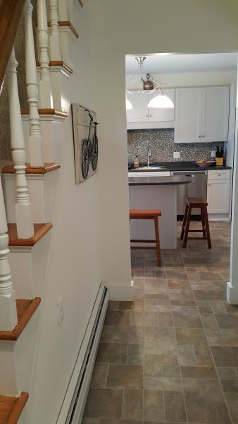 Front hallway leads to kitchen with island and riverstone backsplash.