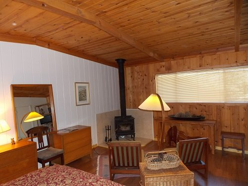 Master bedroom has stove fireplace and sitting area.