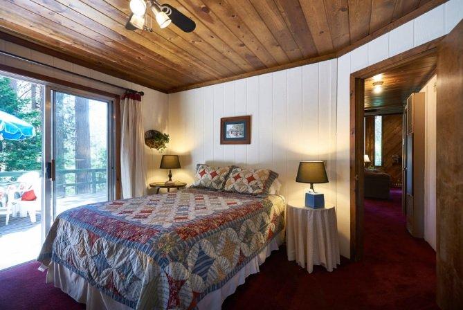 La chambre principale avec lit queen et un accès terrasse.