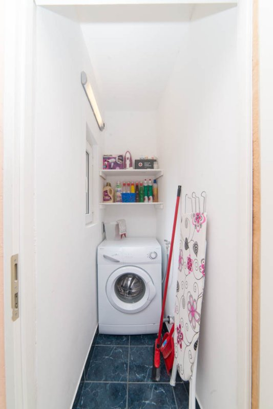 Small storage with the washing machine, detergent, iron, hairdryer, first aid kit...