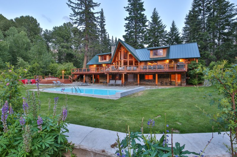 The Lodge viewed from back yard in summer, expansive deck with pool, hot tub