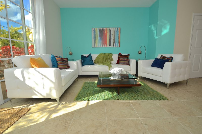 Open Living Offers Two Leather Sofas, Leather Chair, LED High Def TV & Direct Access To Patio Area