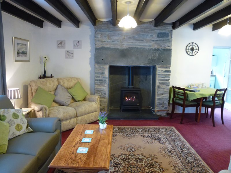 Living/Dining room with original slate backed fireplace, with a gas-fired, wood-burning style fire