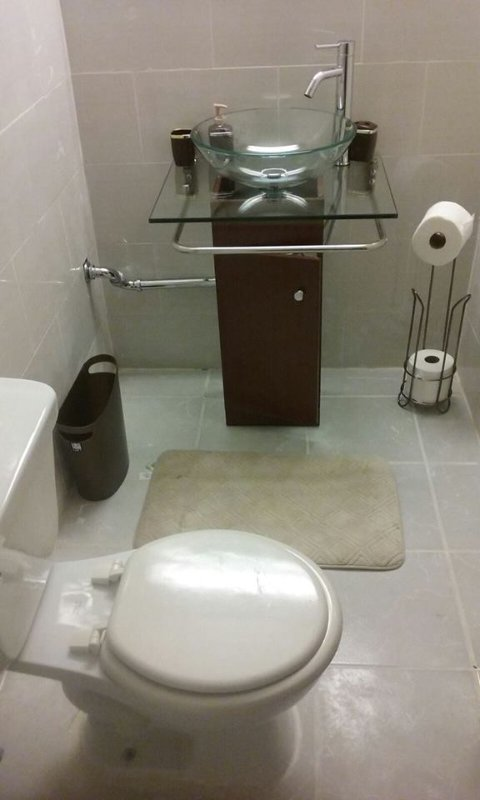visão mais ampla de casa de banho com duche outro lado do toliet.