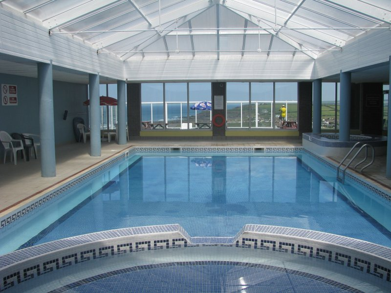 Swimming pool, jacuzzi, looking out onto patio area and views of Widemouth Bay.