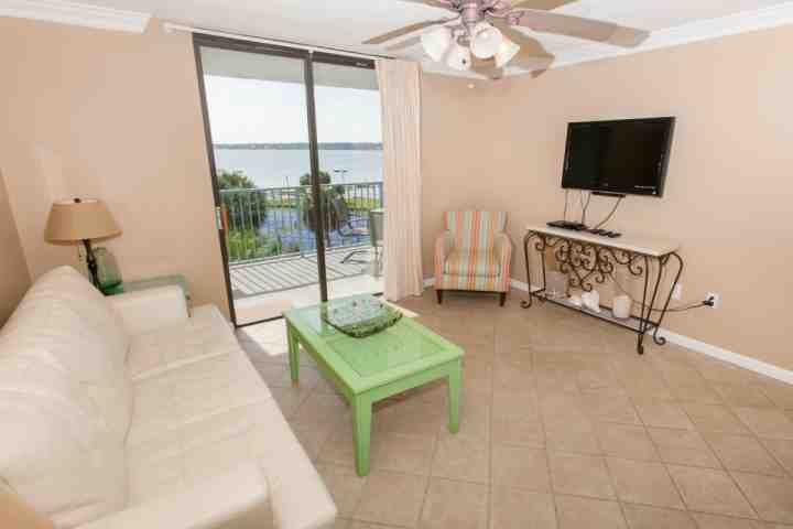 Living room with tile floor, sofa, recliner and chair and private patio overlooking Little Lagoon