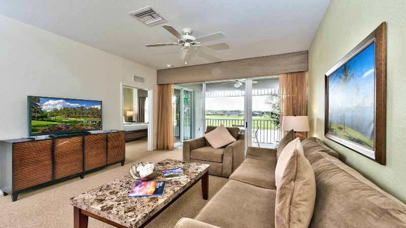 Living Room with Flat Screen TV, Fan, and Entrance to Lanai Area with Lake and Golf Views; Couch is a Pull Out! New Decorations in 2015!