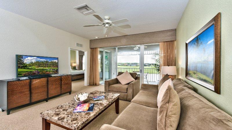 Sala de estar con TV de pantalla plana, ventilador y entrada al área de Lanai con vistas al lago y al campo de golf. ¡El sofá es un extractor! Nuevas decoraciones en 2015!