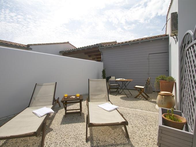 Terrasse privative avec transat et salon de jardin