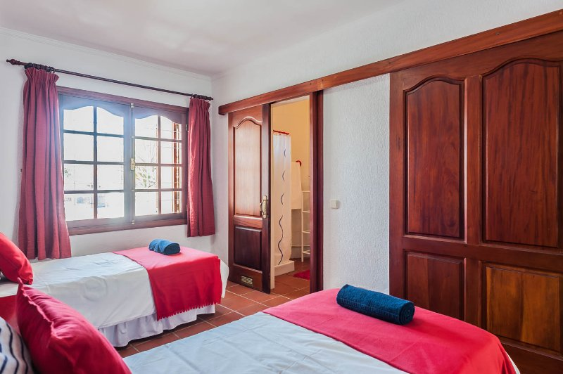 Twin bedroom within main house, with wardrobes and en-suite shower room.