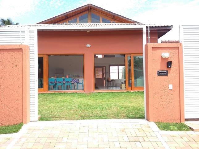 Portão eletrônico aberto. Casa ampla, arejada com arquitetura diferenciada.