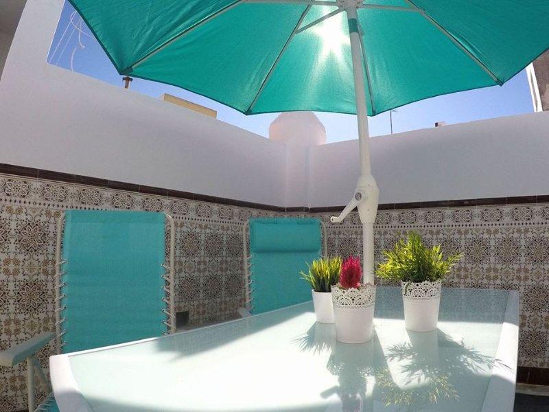 Patio privado con mesa, sillas y sombrilla