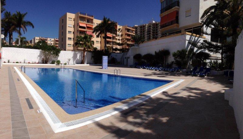área da piscina ensolarada com casas de banho.