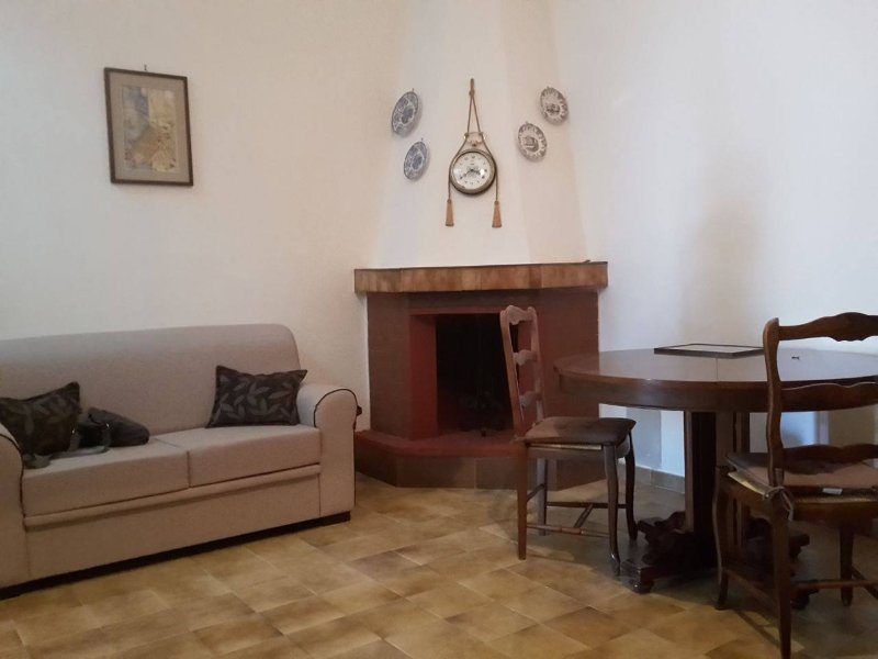 living room with fireplace, round table, sofa bed and TV set inside the equipped wall