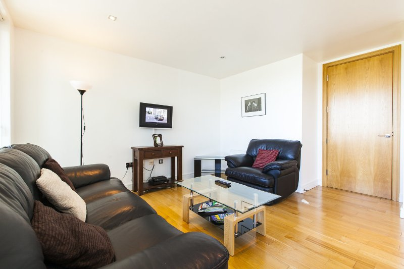 Spacious living area with wall mounted TV