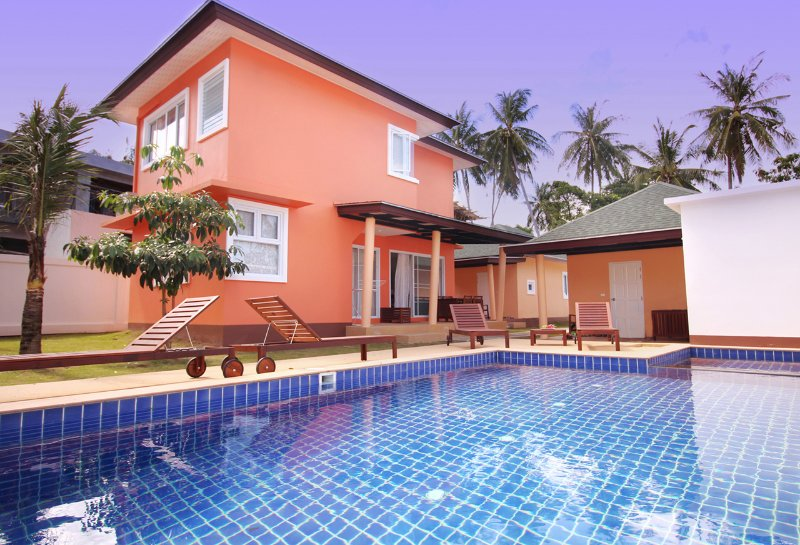 Two 2-storey houses with terrace which stand in center of the area in front of a swimming pool.