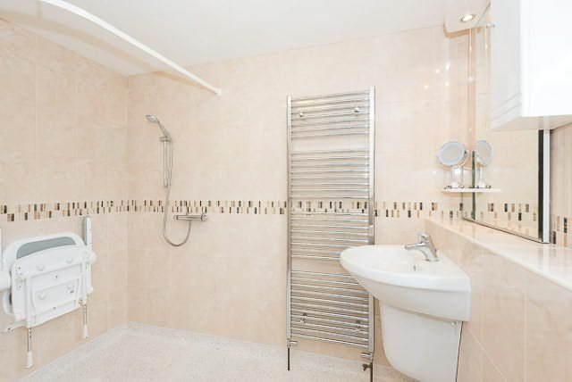 salle d'eau spacieuse dispose d'un porte-serviettes chauffant et un siège de douche.