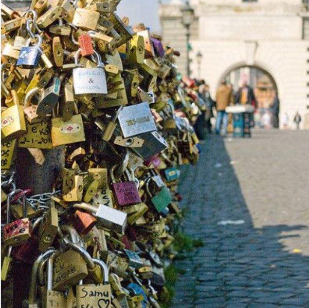 So romantic,couple put padlock  with  their name on Ponte Milvio bridge .