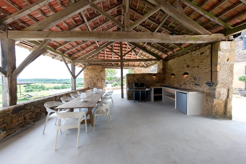 The summer kitchen, a wonderful shady place with a table and chairs for 12 people and a Weber bbq