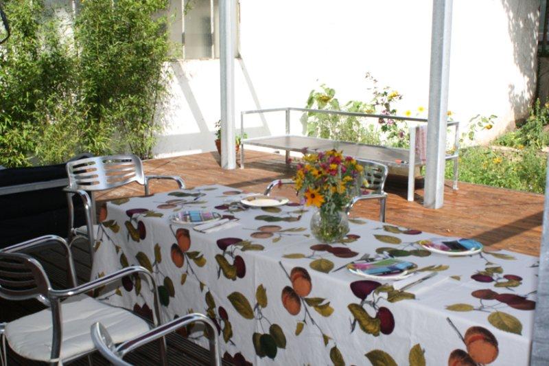 Terrass trädgård med stort matbord